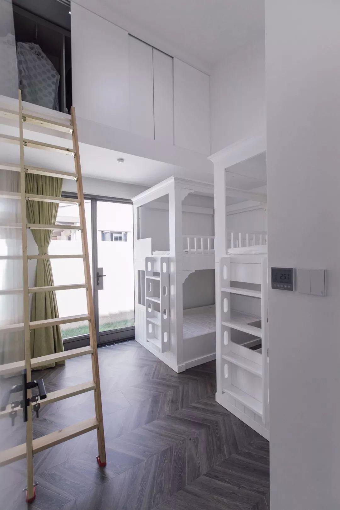 儿童房两张白色子母床进行了并排设计,并在中间留出走道,让孩子们拥有自己各自独立的空间。