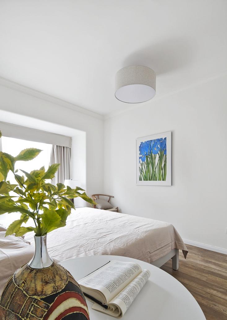 床头的小植物和对面墙壁挂画,相呼应的同时,也为空间加了一丝纯色之外的色彩。
