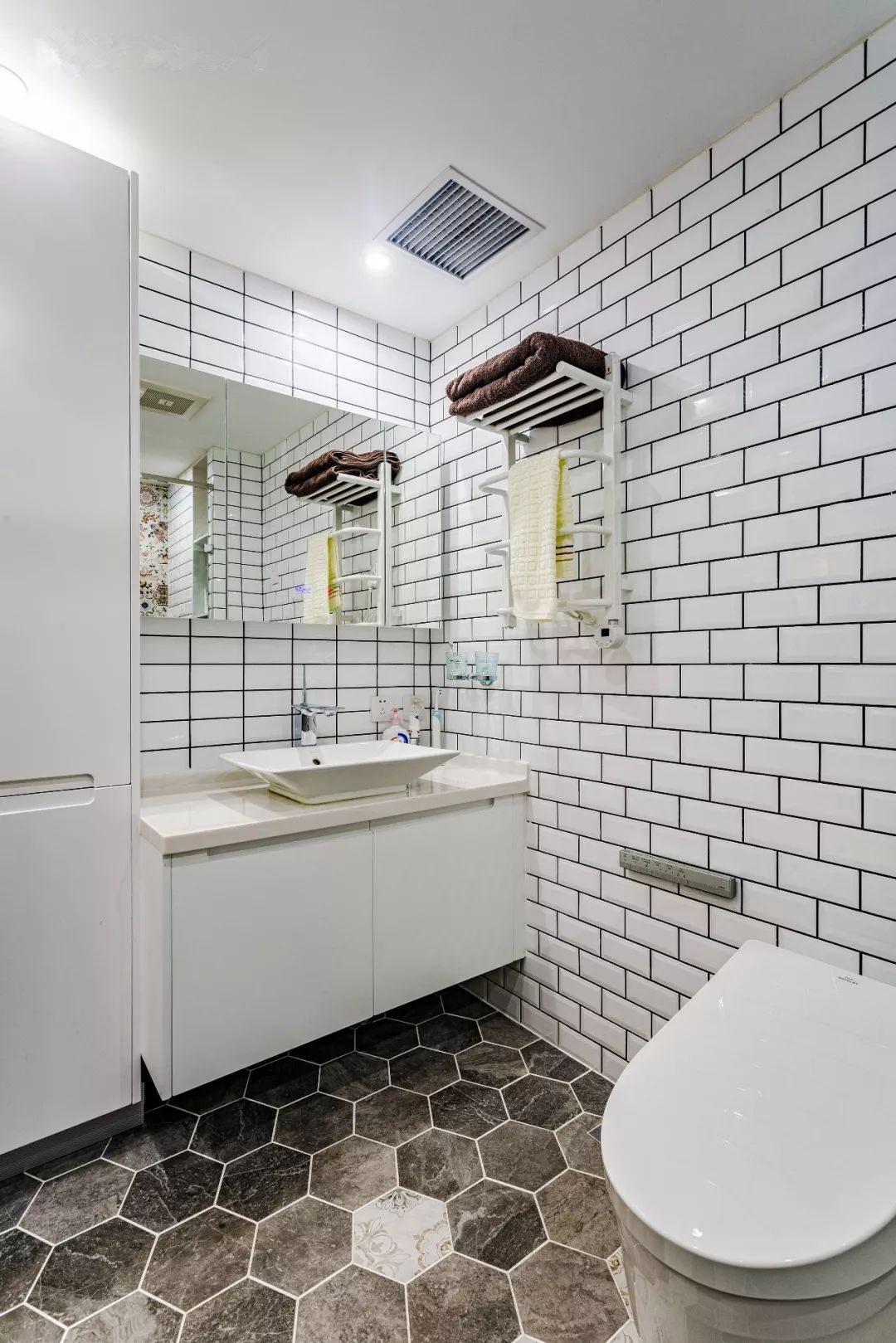 卫生间是没有自然通风采光的暗卫,所以配备了电热毛巾架;左侧的高柜则承担了大量的日常用品收纳功能。