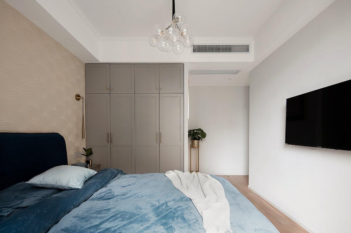 次卧整体基调偏冷淡,蓝色床品理性又沉稳,嵌入式衣柜大气又实用。