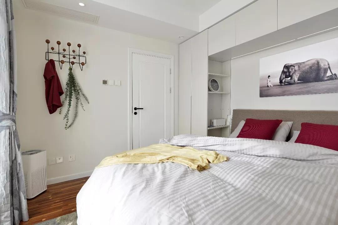 床头选用一体化的衣橱床柜,收纳格设计简单实用。卧室并没有太多装饰,选用简易衣架,挂衣帽也是很实用的哦