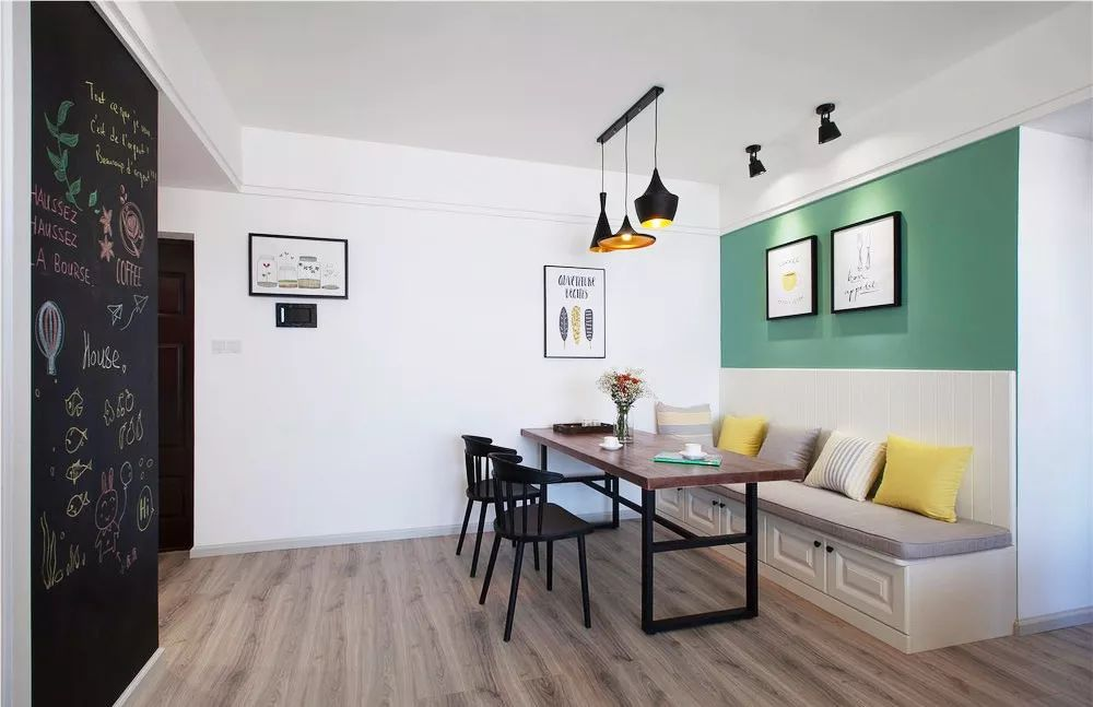 鹅黄色的抱枕和墨绿色背景墙给人清新感受。