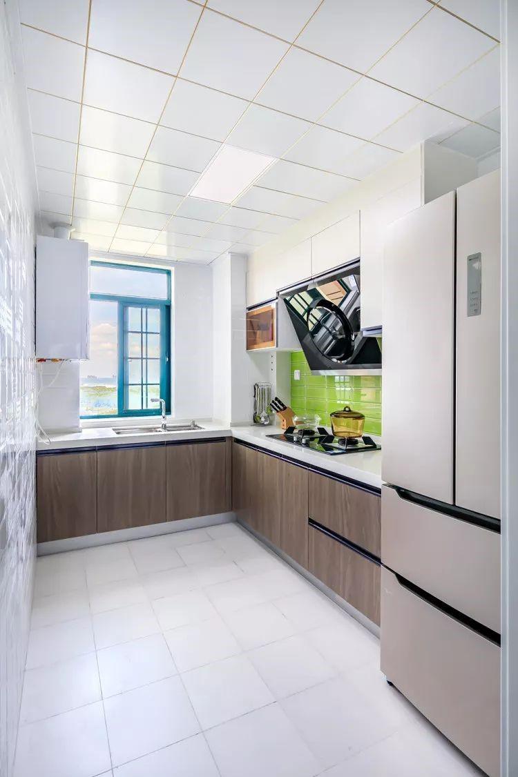 白色石材的台面与吊柜中间跳青柠绿色瓷砖,将厨房衬托的十分清新。