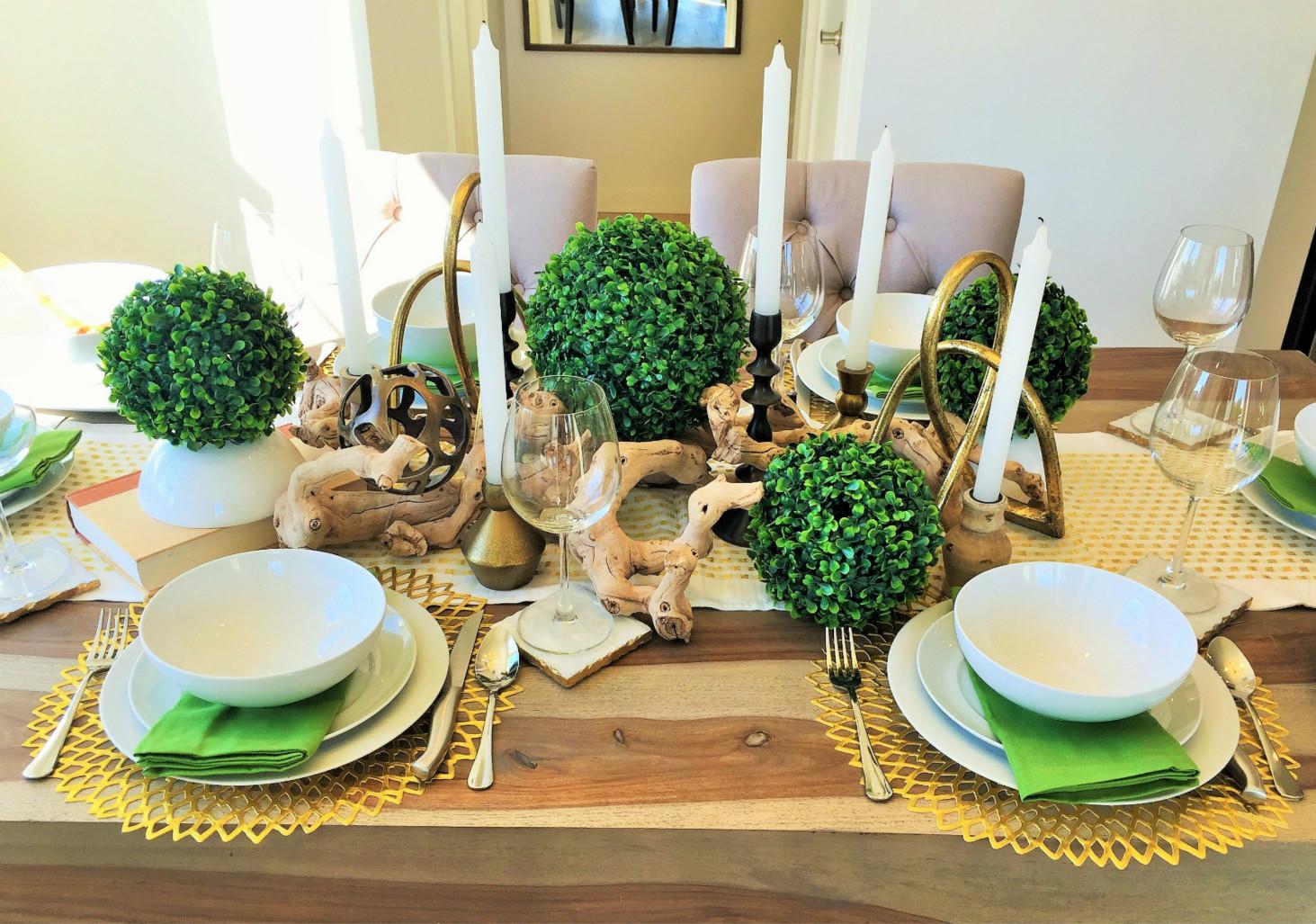 白色的蜡烛、绿色的小盆栽装饰、透明酒杯、瓷器碗盘,绿色的用餐布,设计的很用心。