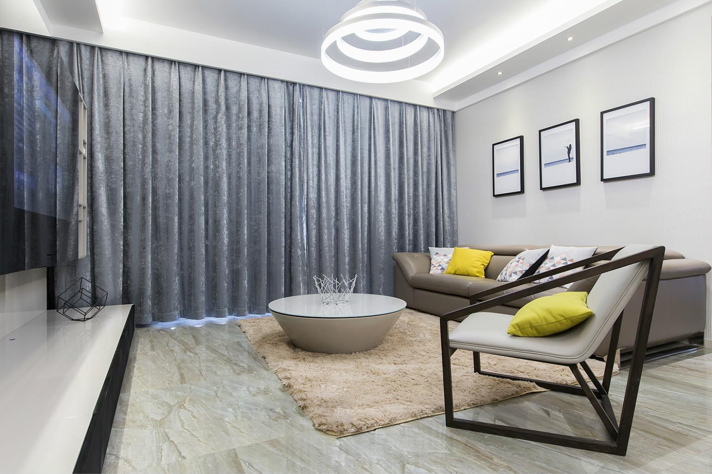客厅皮质的沙发搭配椭圆形的茶几在配上小白地毯很是温馨舒适