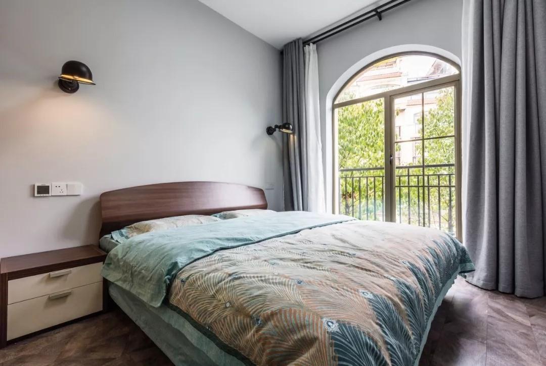 次卧装修简洁,灰色床头背景墙上装饰两盏灯,窗外绿意盎然,打造十分闲适的居家生活。