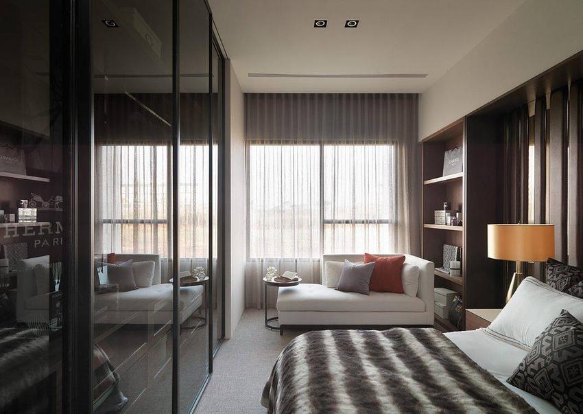 经纱帘过筛的柔和日光窗前,难得的空间余裕,书架、沙发与小茶几于窗前构筑悠闲的休憩角落。