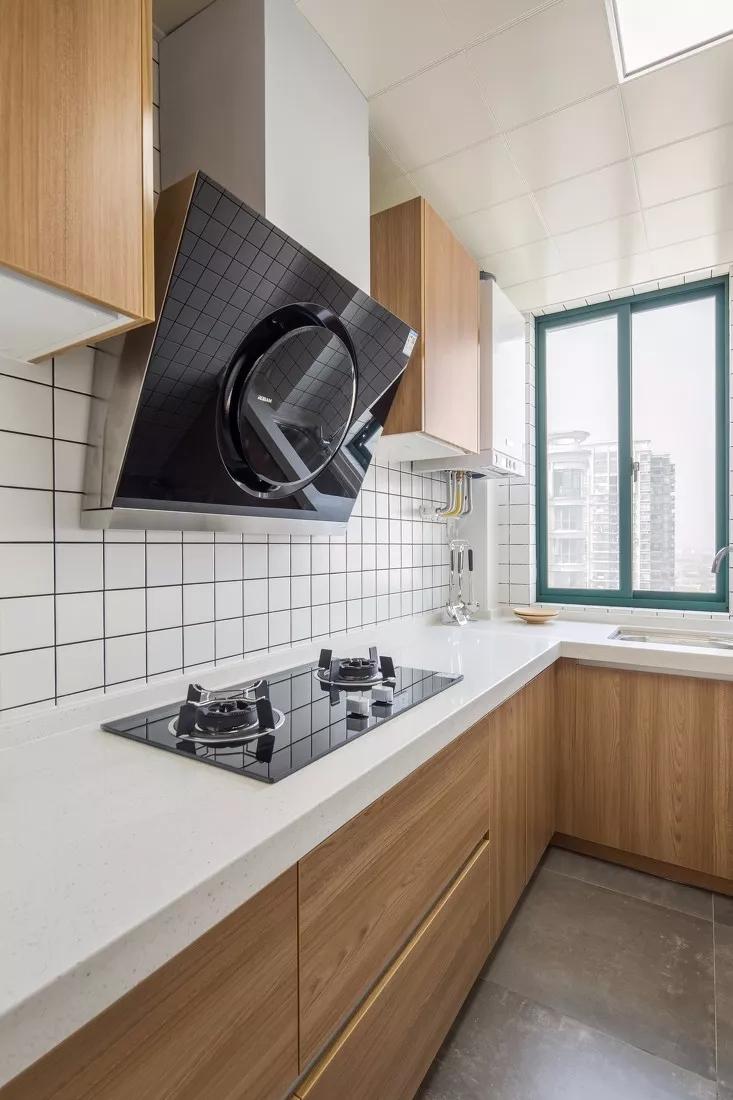 厨房同样延续了原木色元素;虽然面积不算大,走廊尽头的大窗增加了室内光线,整体干净敞亮。