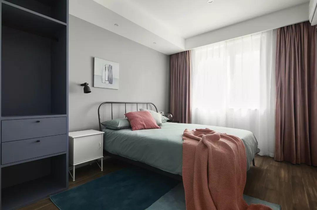 次卧清新恬淡,藕粉色窗帘及砖红色抱枕、毯子的点缀,多了一些温馨舒适感。