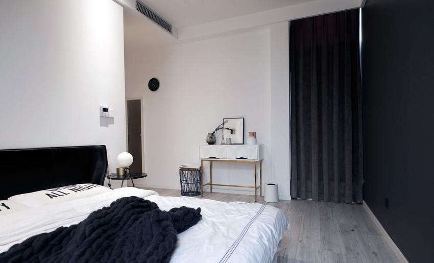 次卧大面积采用黑色和白色,并用原木色作为点缀。