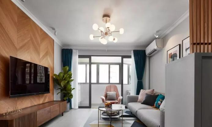 电视墙以鱼骨形木地板做为装饰,为冷灰调的空间增添了温馨舒适的气氛。