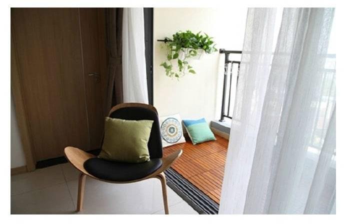 阳台采用有质感的木地板,夏天可以坐在上面喝茶聊天。一层白色的纱织窗帘,一抹植物绿,仿佛走进了大自然。
