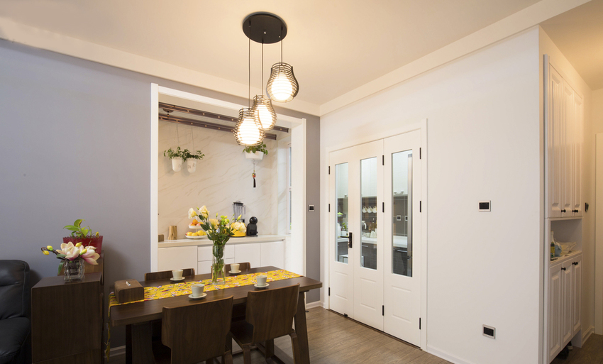 餐厅三盏灯的高低设计和侧边橱柜三开门对称。