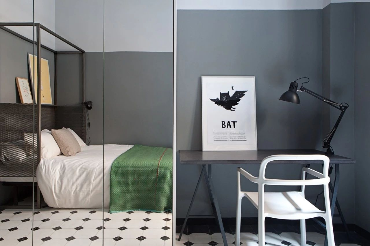 第三间灰色系的卧室。地板以棋盘为设计灵感,床头位置加了个铁艺书架能放书或其他小物品。