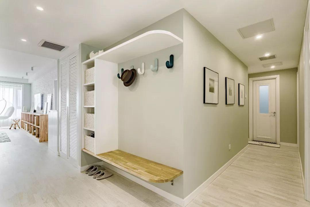 进门玄关处,设置坐榻,方便一家人换鞋。换鞋凳一侧做了圆弧处理,可以增大拐角处的过道尺寸,放置磕碰。
