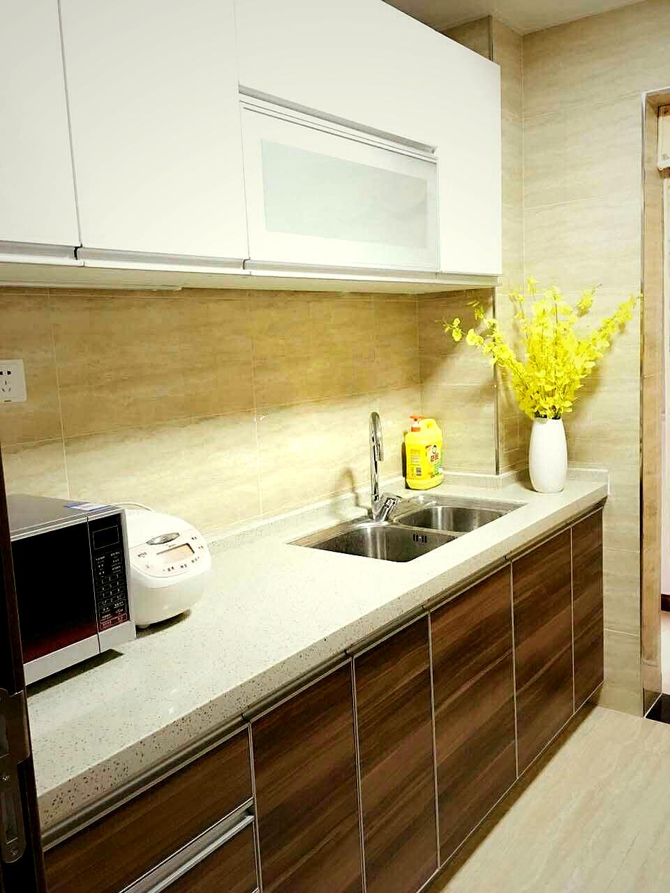 白色石材台面,延伸出来胡桃木色橱柜,白色吊柜完全利用到厨房空间,收纳功能完全没问题。
