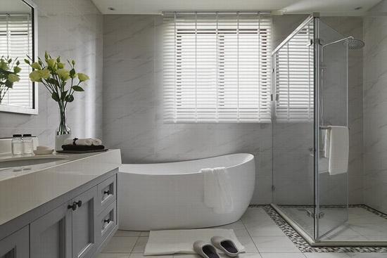 卫浴空间延续整体色调,以干净的灰白色铺垫,并设置独立淋浴间与泡澡浴缸。