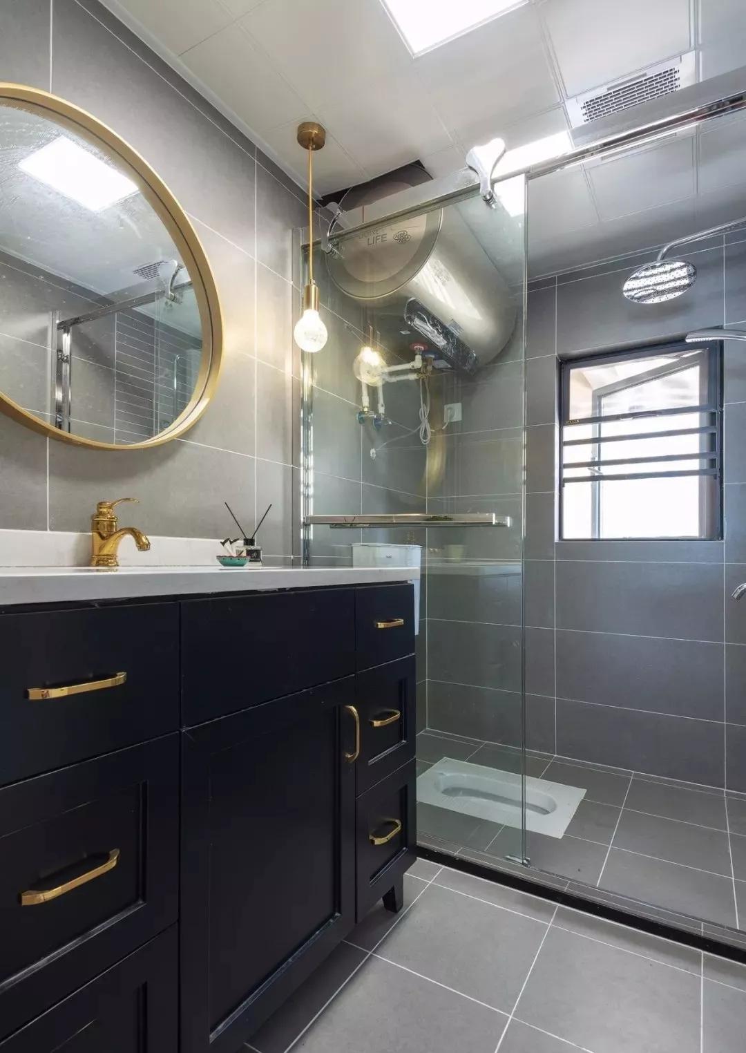 卫生间以玻璃淋浴房做到干湿分离,整个空间以灰色为主调,橱柜采用深蓝色,金色元素点缀其中。