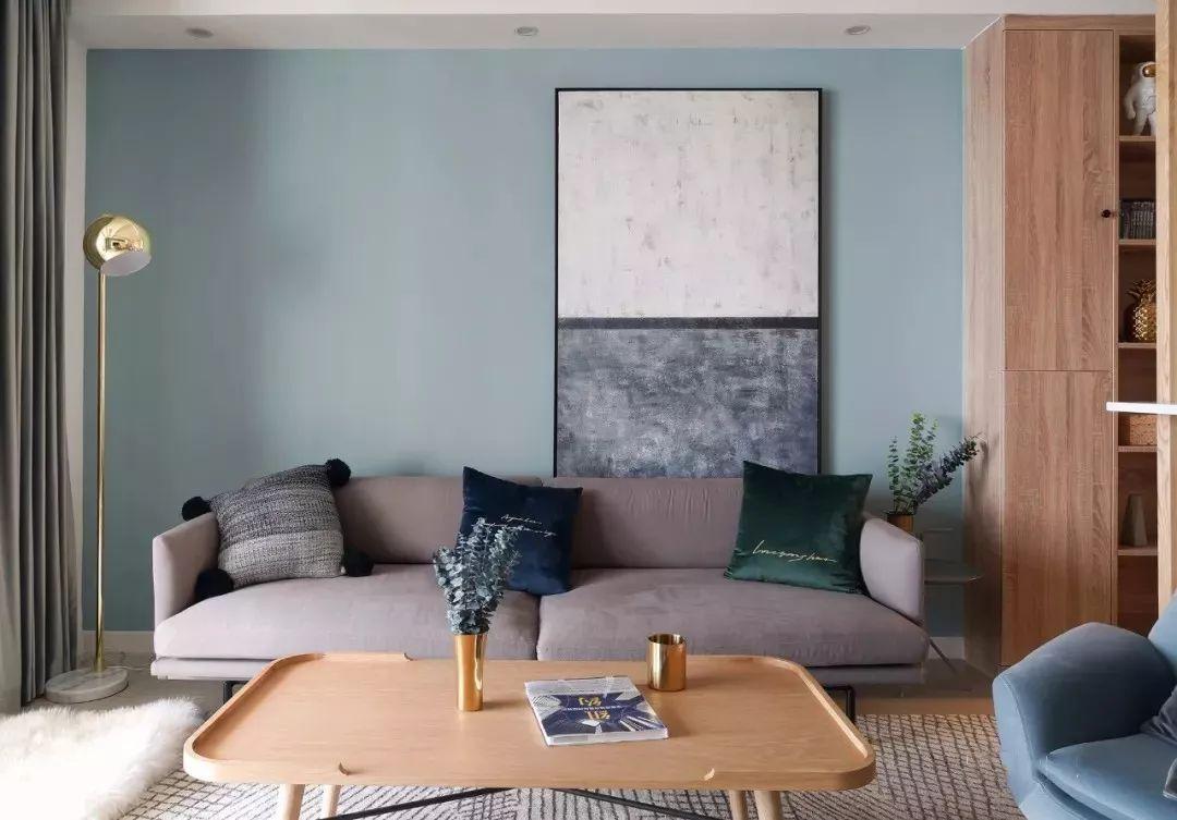 浅蓝色背景墙点缀巨幅装饰画,灰色布艺沙发上摆放丝绒材质抱枕,精致高档。