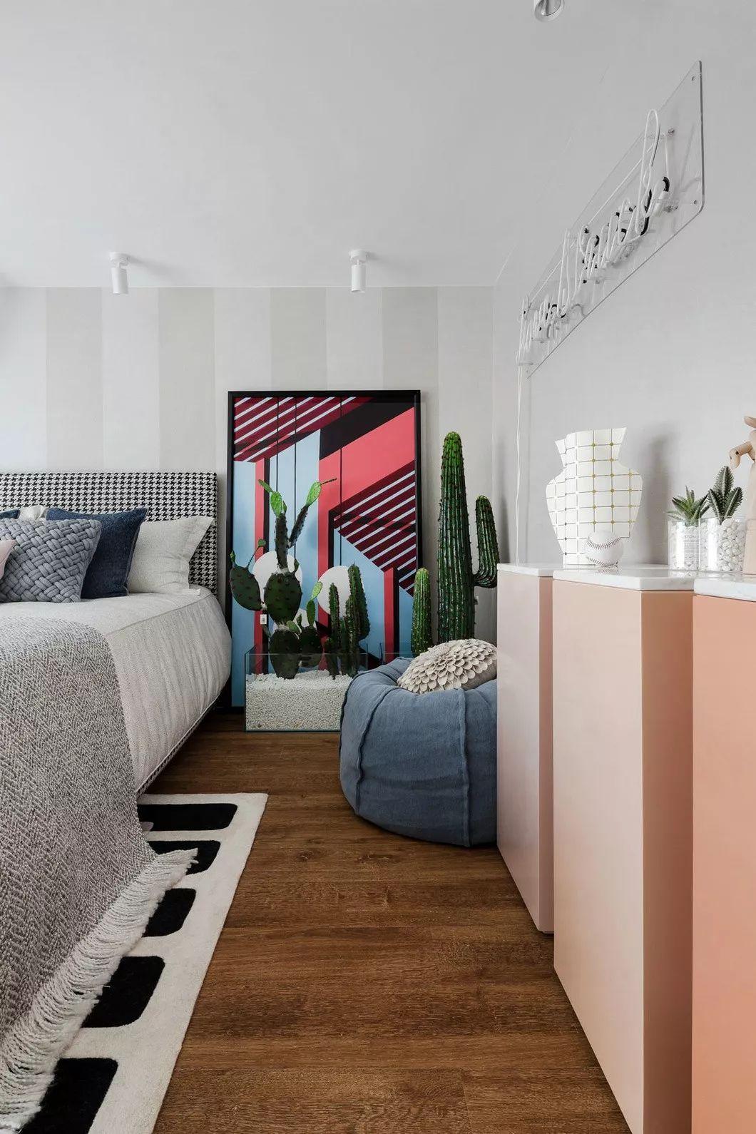 主卧内,柚木色和粉色给人一种独特的温柔,发光字体装置与略显夸张的仙人掌绿植,自带一份电影画面质感。