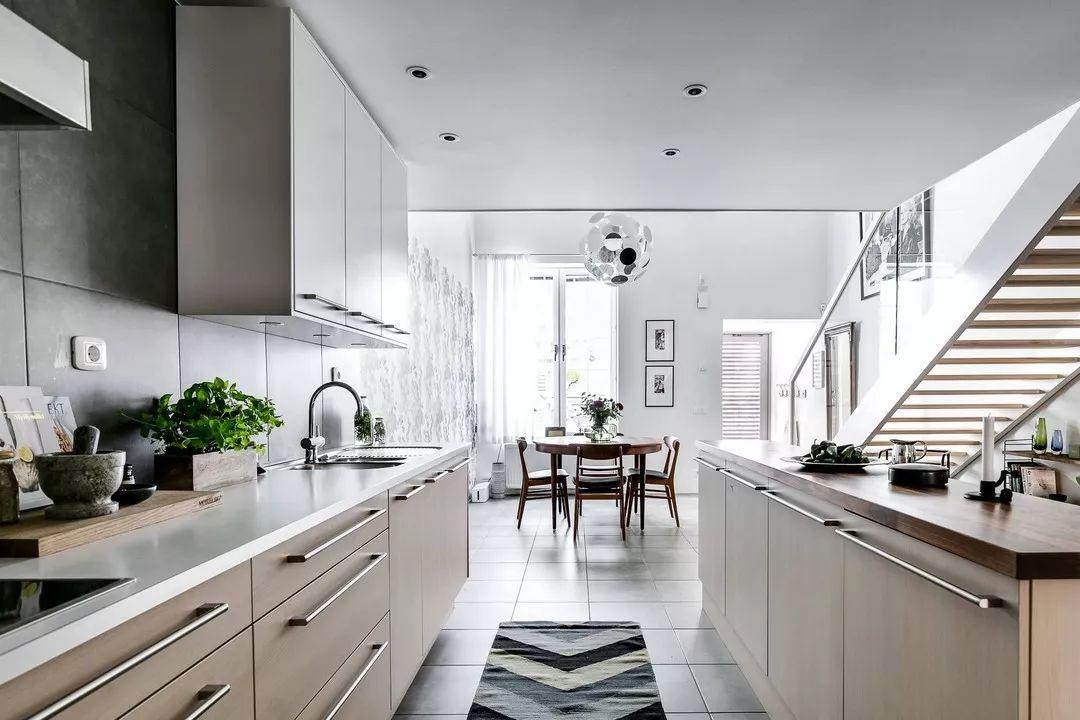开放式厨房在夹层的下方,吊柜、岛台为厨房提供了大量的储存空间。