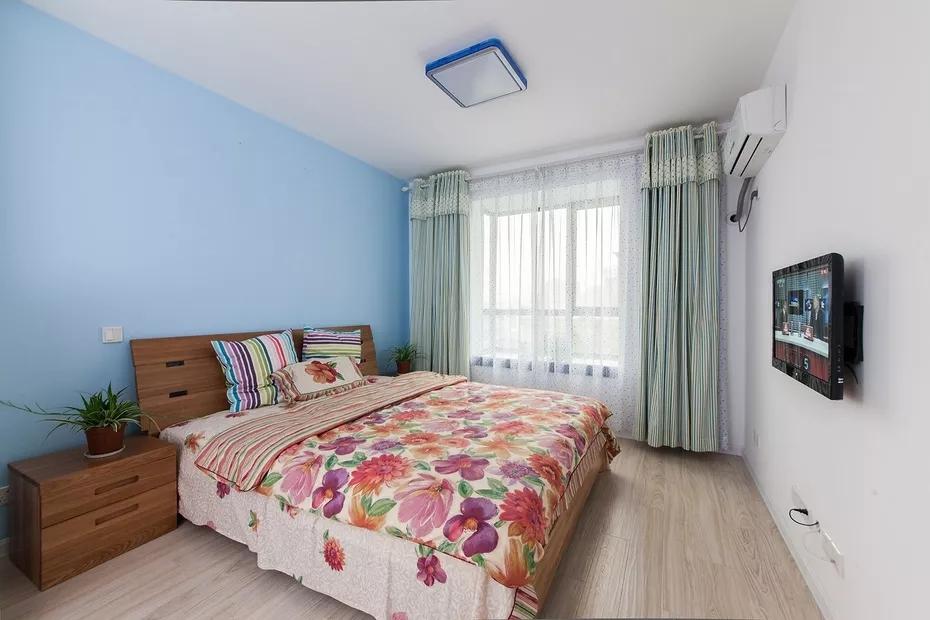 卧室也是以蓝色和白色为主色调,花色床品点缀其中,清新的绿色窗帘,让整个空间更加贴近自然。