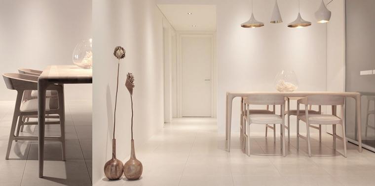 纯白的餐厅,边角柔和的木质餐桌椅,圆润的木质花瓶,通过金属吊灯带来黄色调灯光。