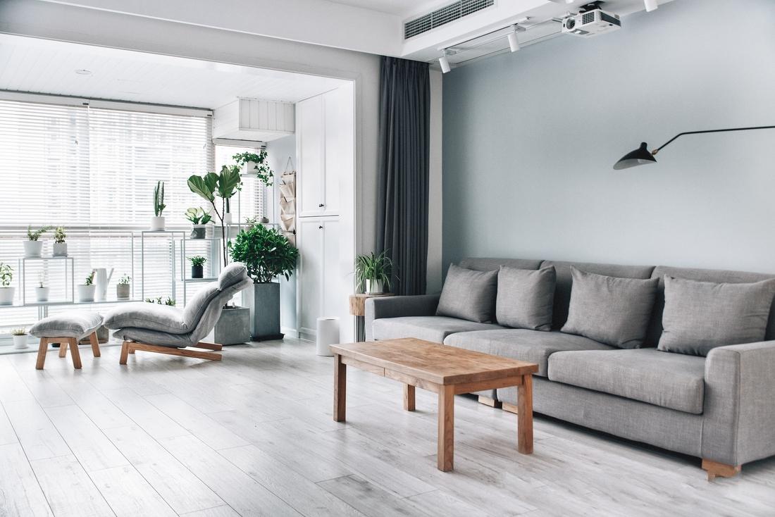 客厅和阳台打通,躺椅背后利用空调位设计了一个洗衣区,并做柜门隐藏。