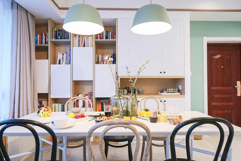 餐桌被放置在紧靠窗的位置,客餐厅一体化,餐厅墙面的书柜与整体风格一致。
