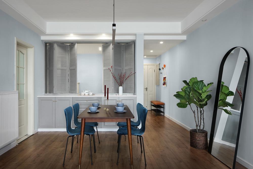 餐厅设计化繁为简,实木餐桌搭配蓝色餐椅,渲染出低调静谧的视觉效果。