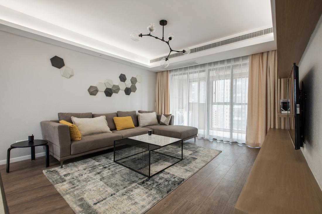 背景墙上不规则的蜂窝形状图案与客厅照明相应得体,同时为空间带入些许工业质感。