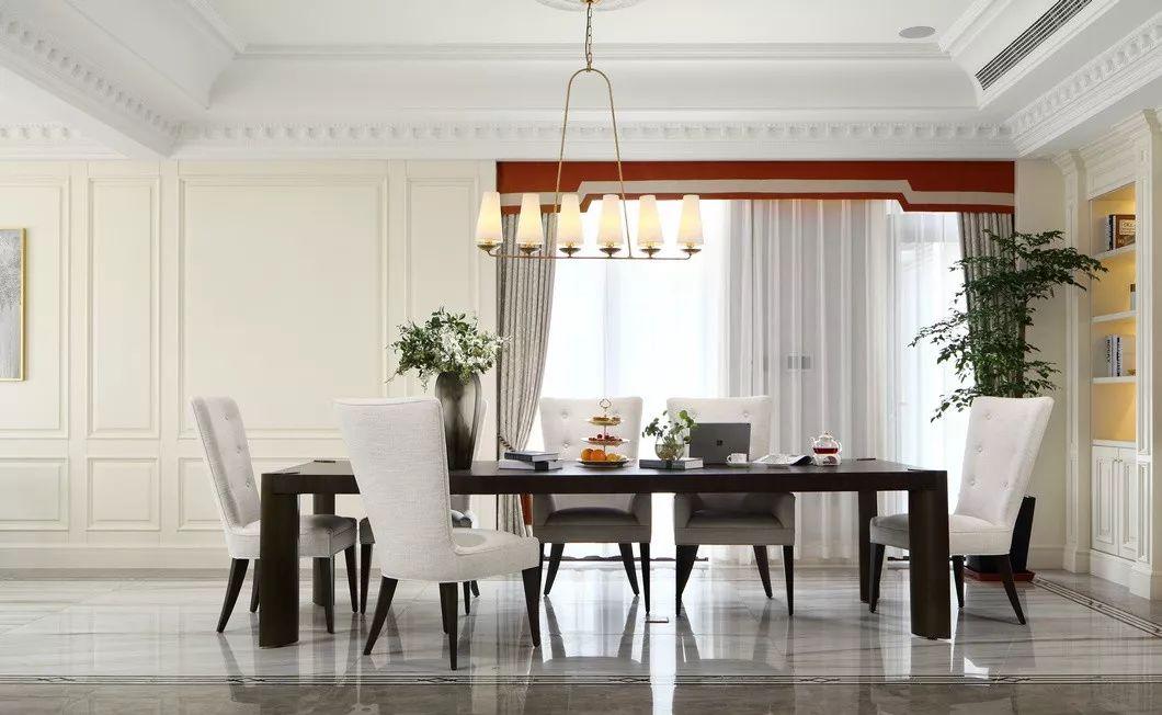 一旁的餐厅里,深色的胡桃木桌和布艺餐桌凳使得餐厅看上去高雅而干净,加上做旧而狭长的吊灯点缀,更显特别