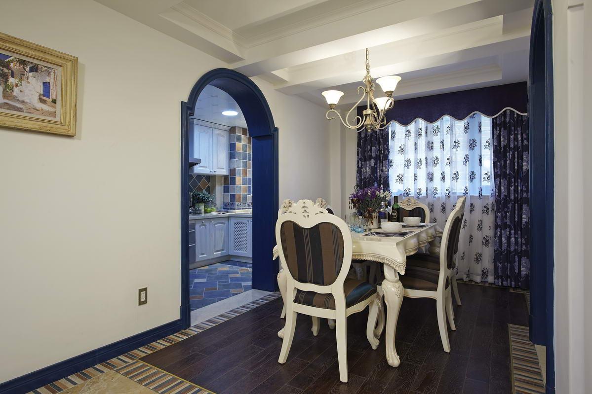 客厅的左边是餐厅区,白色调的桌椅,蓝色调的桌布和鲜花,让人倍感舒适温馨。