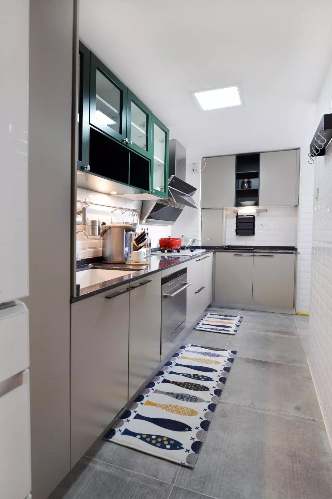 厨房吊柜延续了客厅的墨绿色的复古高雅;鱼形地毯放置厨房,非常应景。