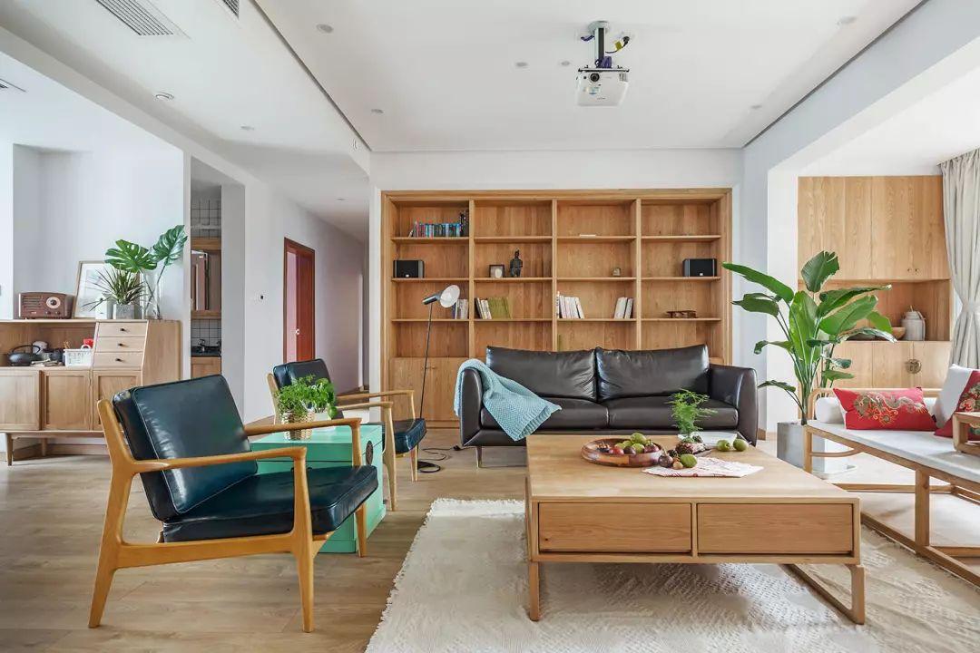 客厅,所有的家具都是走原木路线,洋溢着大自然的气息。用书架代替沙发背景墙,让空间得以有效利用。