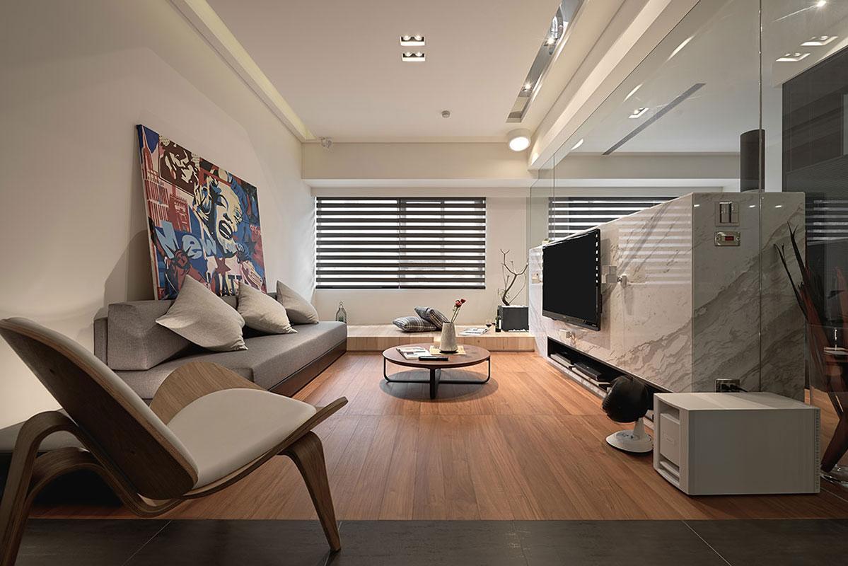 客廳以木質的地板搭配淺灰色的沙發整體干凈亮麗