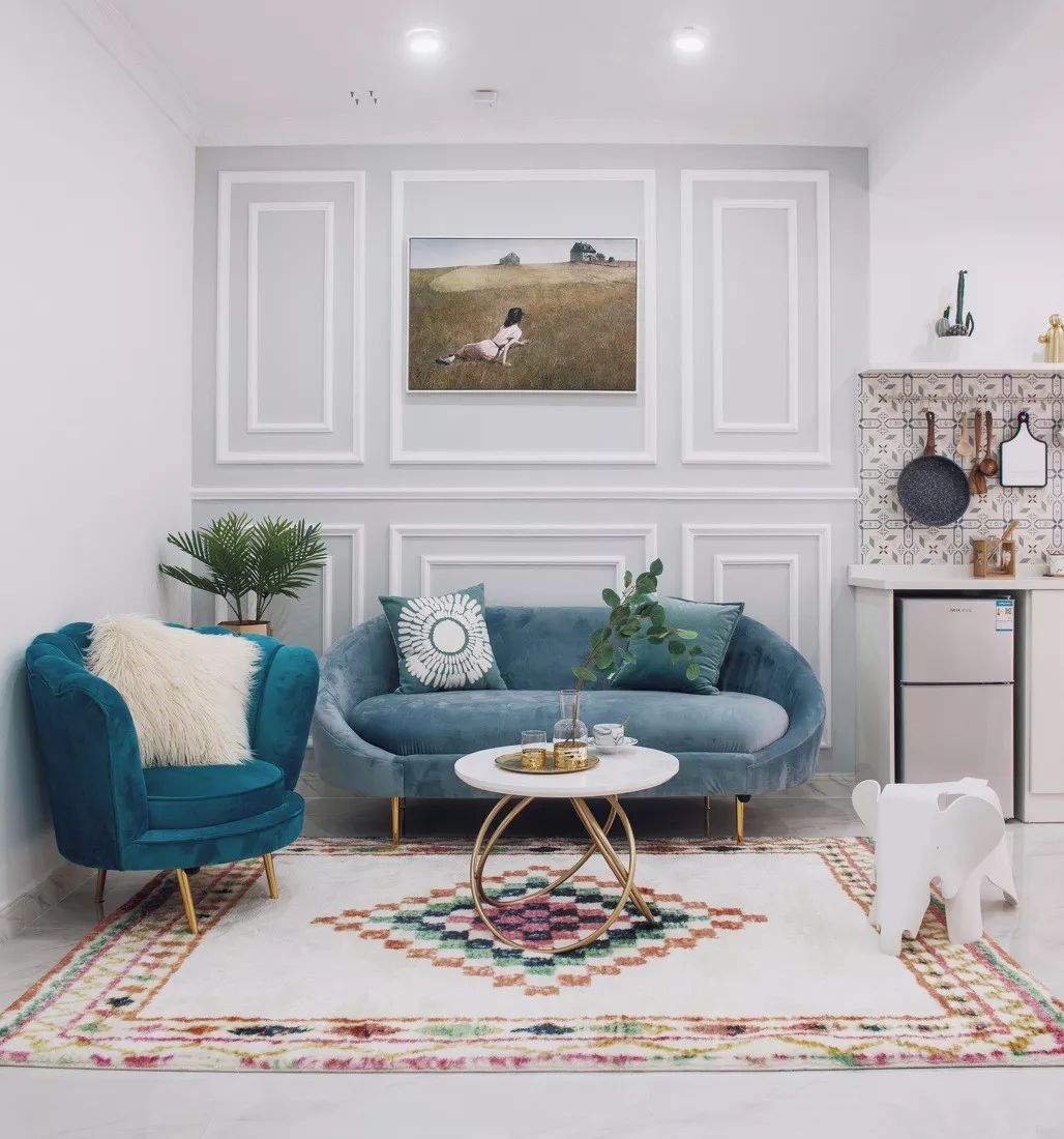 民族风格地毯搭配湖蓝色沙发,以及精致耐看的美式茶几,很高级的配色,整体空间不会很单调。