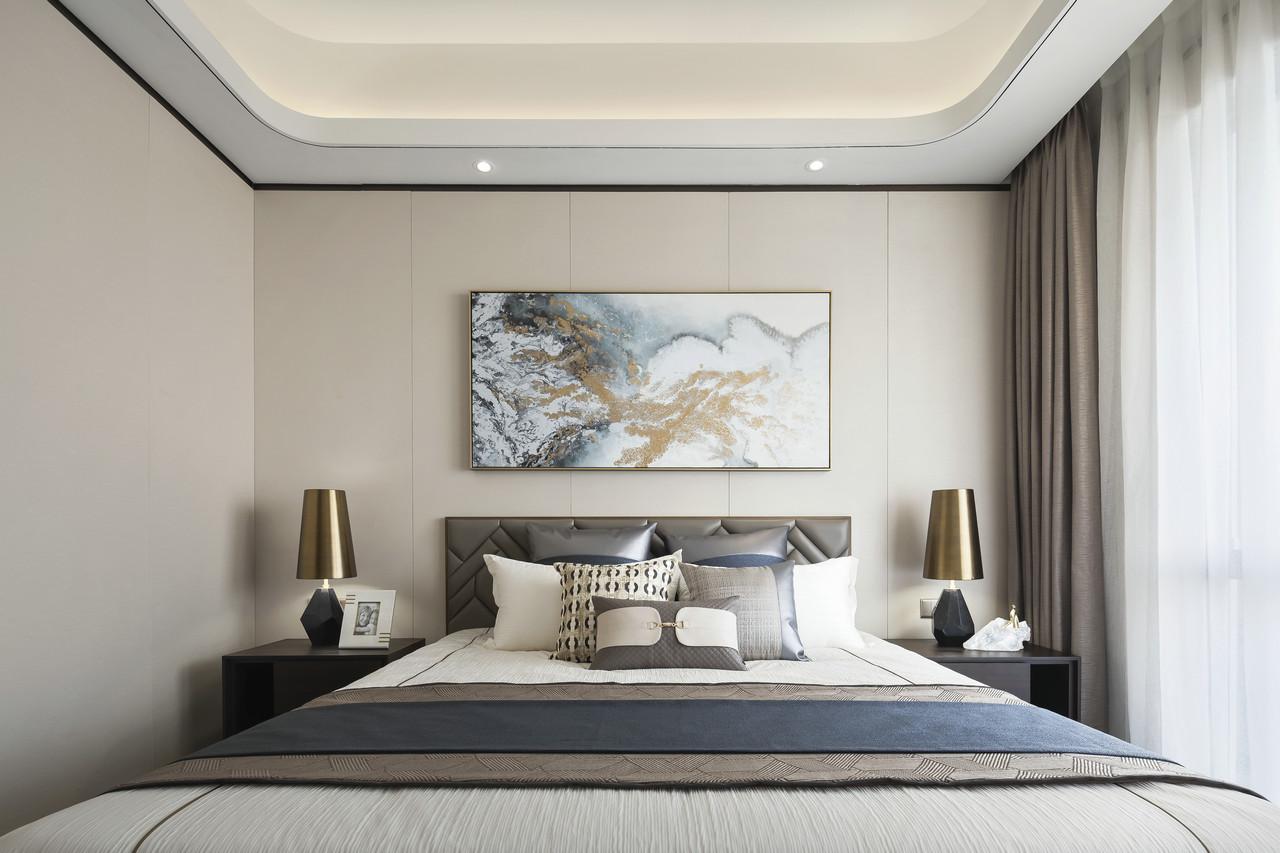 奶白色集成板材背景墙,用一副山水装饰画点缀其中提升了空间艺术感,简约床头柜、金色台灯,时尚又充满质感