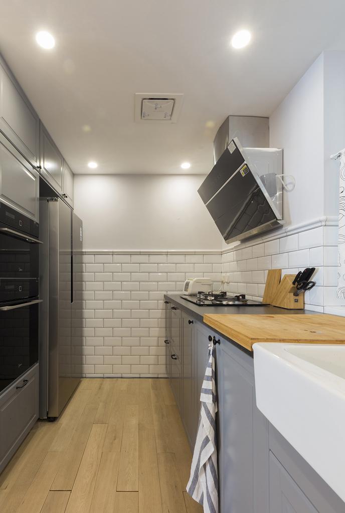 小白砖铺贴半墙搭配灰色的橱柜,家电嵌入式设计,空间收纳井井有条。