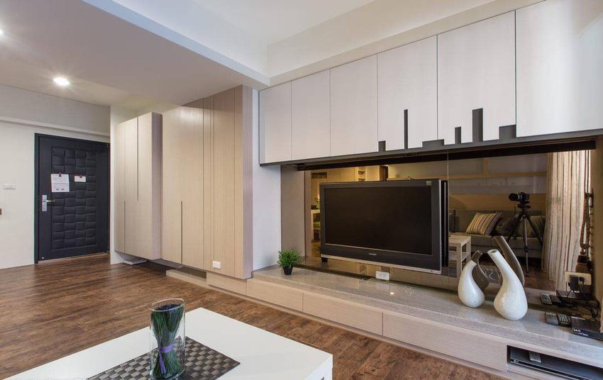 玄关和客厅被短屏风隔断,贴墙的收纳柜高低的几何设计突出了区域的空间感。