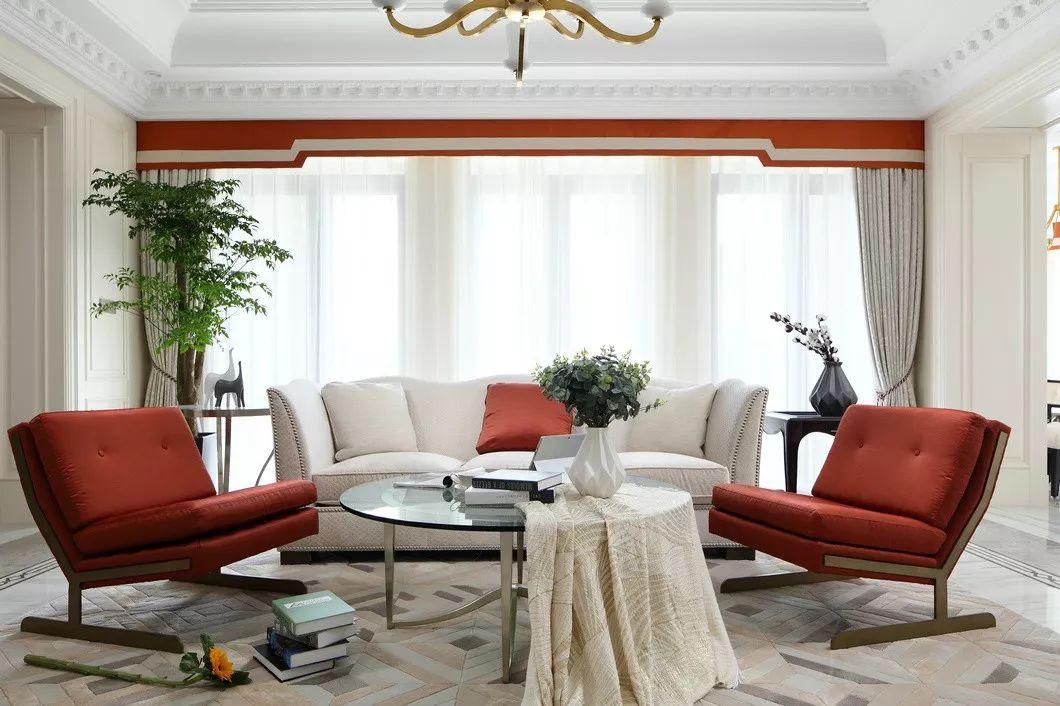 宽敞的起居室由米白色的墙板包层,将跳跃的橙色单椅、浅灰地毯以及干净的白色布艺融合在一起。