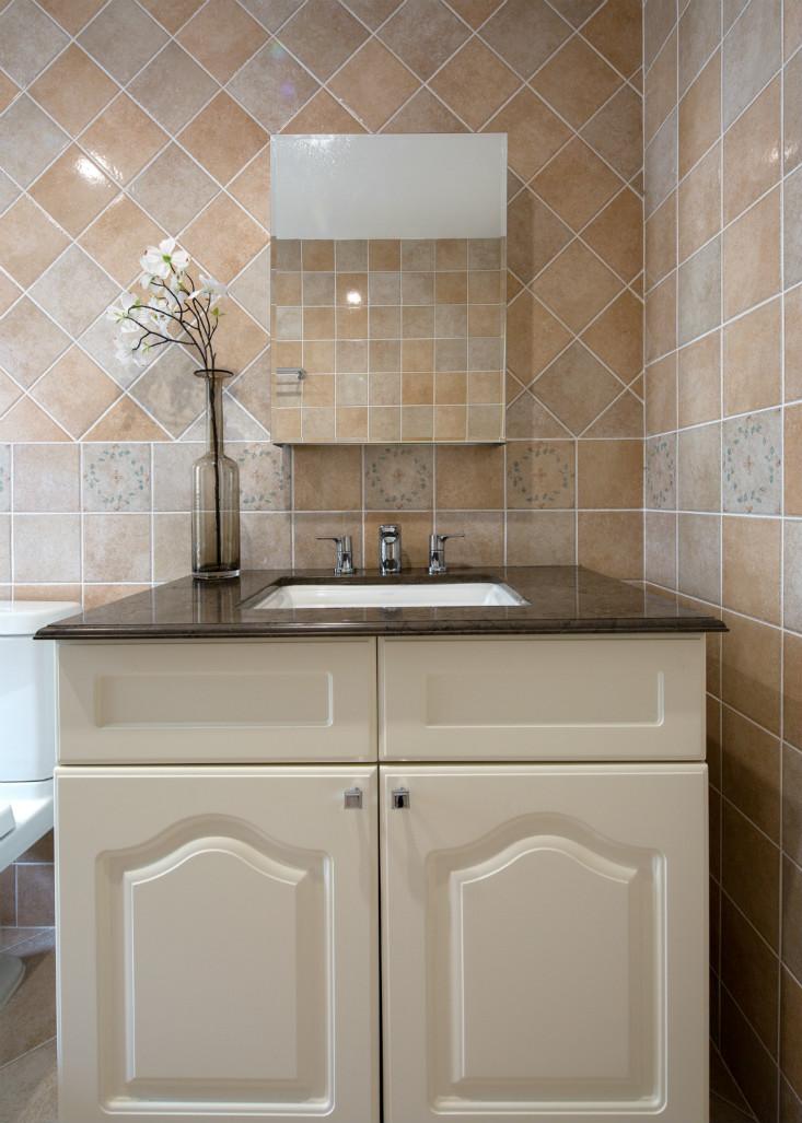 浅色的方形瓷砖,白色的橱柜,整个卫生间与整体的风格很协调。