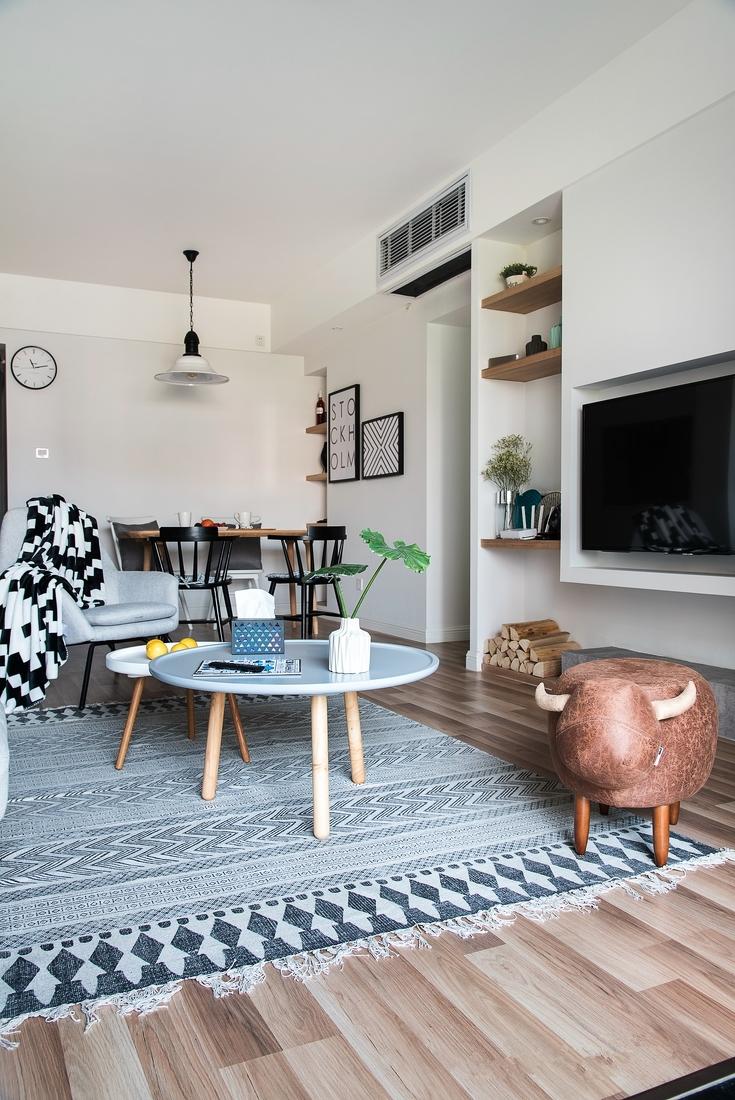 柔软舒适的灰蓝色地毯铺在茶几下,沙发坐腻了也可以席地而坐,温润的木纹肌理可以作为空间的基底.。