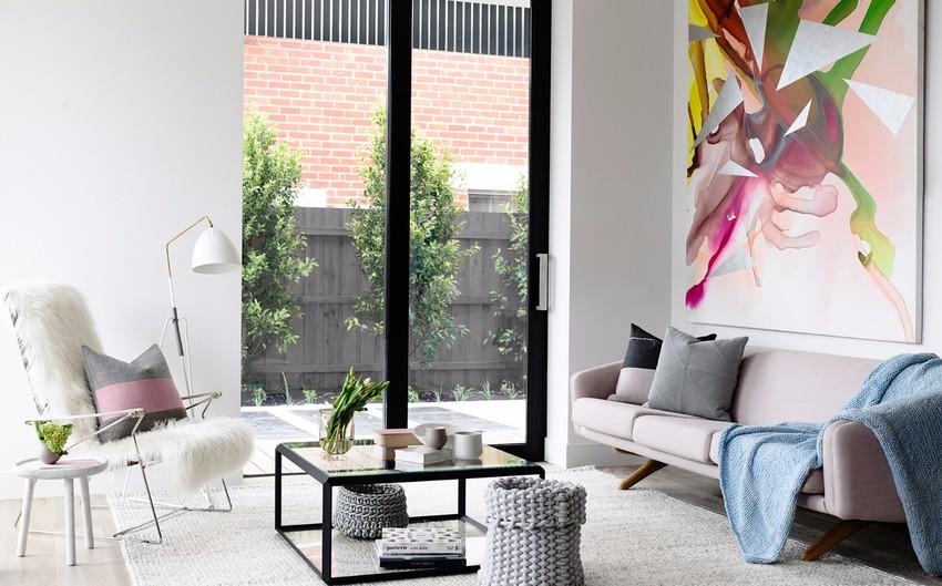高耸的黑框玻璃门,搭配裸粉色沙发、缤纷艳丽的装饰画,客厅的美丽实在令人难以忽视。