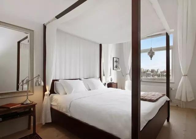 卧室很有异域风味的实木床架,拉上帘帐,微风阵阵,一种梦幻的浪漫感觉萦绕身边。