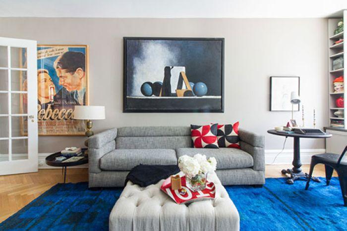 浅咖色墙面上挂着艺术海报与装饰画,海蓝色地毯尽显深邃,而红黑色抱枕又带出了几分活力。