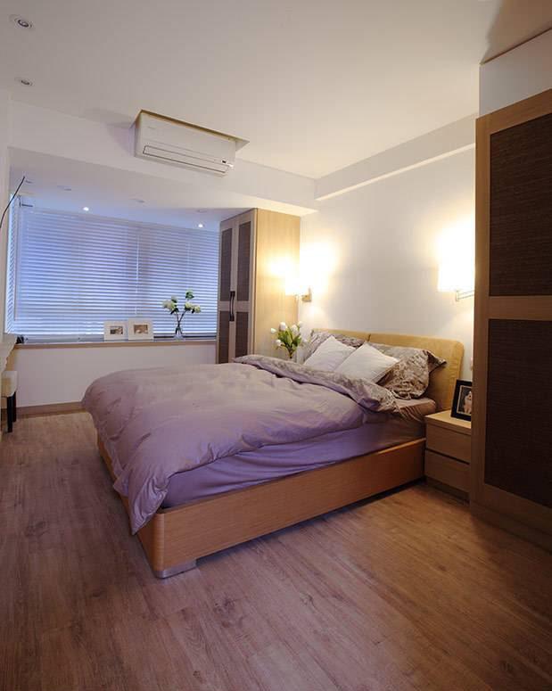 卧房以温润的木质元素为主,床头运用对称的衣橱及壁灯,提供足量收纳与光影情境。