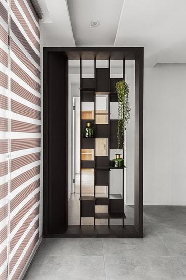 入门处设置一道镂空造型屏风,局部穿插错落的表示层板,可以摆放装饰品或植栽,形塑玄关的端景意象。
