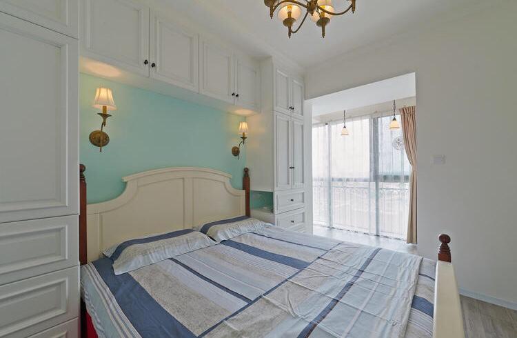 卧室蓝色墙面搭配白色衣柜及床,吊灯是垂坠式的,整个卧室简洁温馨又不失舒适感!