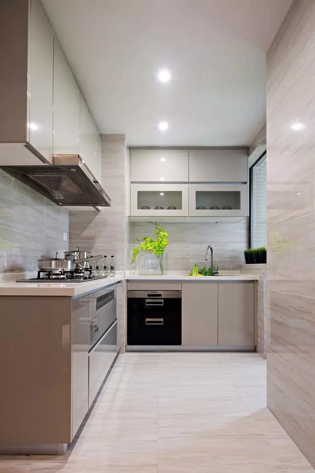 厨房摆放的绿植,不锈钢的厨具,整齐明亮。在水槽上面打造一个壁橱节省了空间。